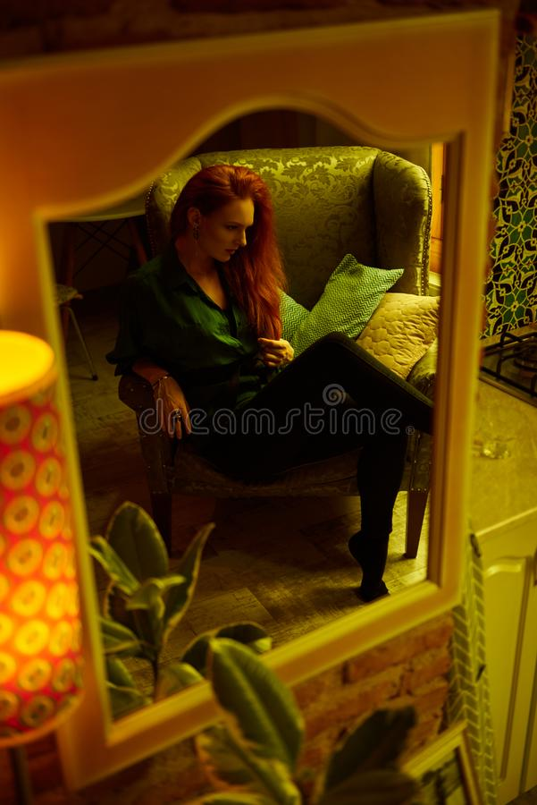 Vintage photo of Beautiful red haired young woman posing in old loft apartment in Tbilisi. Mirror reflection of Ginger lady posing in loft apartment in Tbilis stock photography