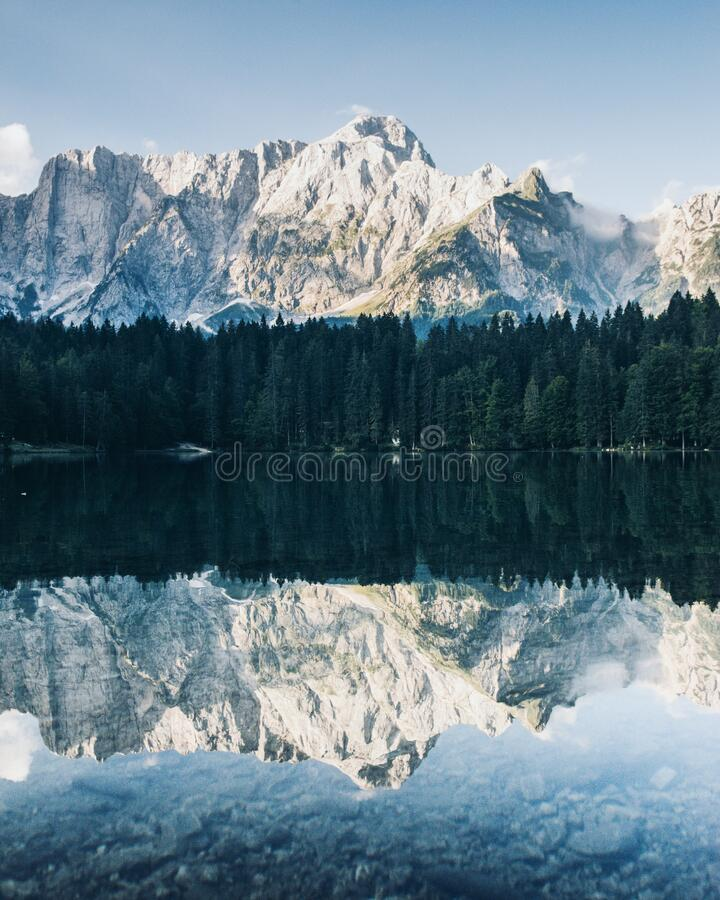 Mirror reflection in Lago di Fusine, Italy. Mirror reflection in crystal clear Lago di Fusine, Italy stock image