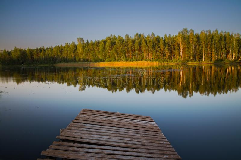 Mirror reflection in the lake. Pier in the foreground. Lake Niinsaare, Estonia stock photos