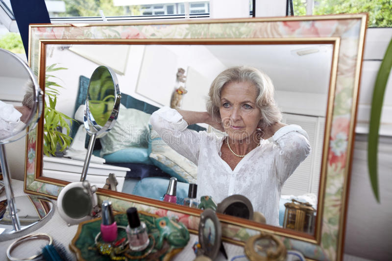 Mirror reflection of senior woman putting on necklace at home stock photography