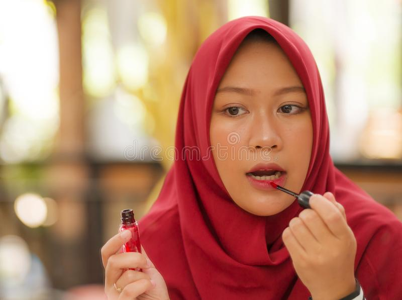 Mirror reflection of young happy and beautiful Muslim woman in traditional hijab head scarf applying make up and cosmetics royalty free stock photo