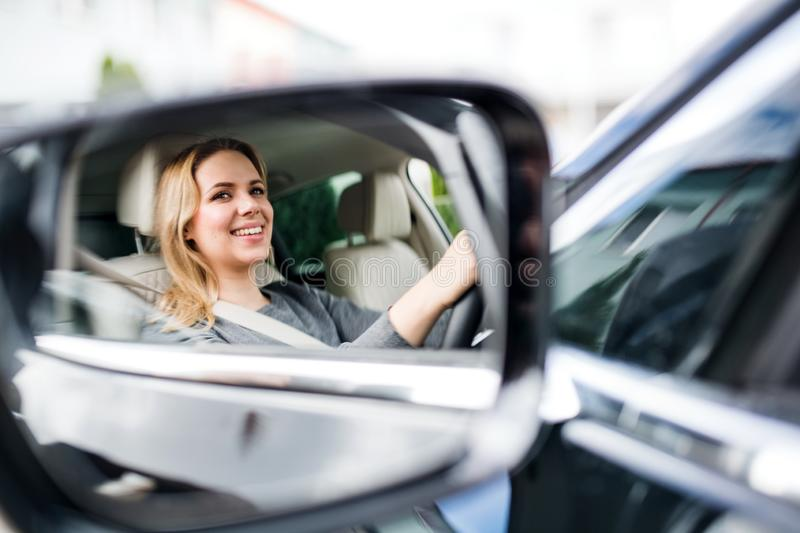 Mirror reflection of young woman driver sitting in car, driving. stock photos