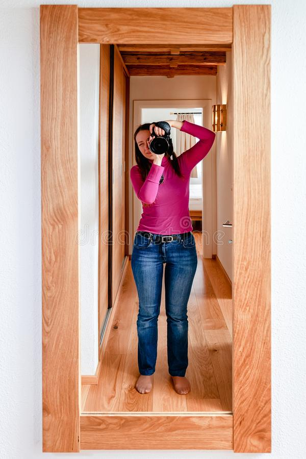 Mirror reflection of Young woman photographer with camera royalty free stock photos