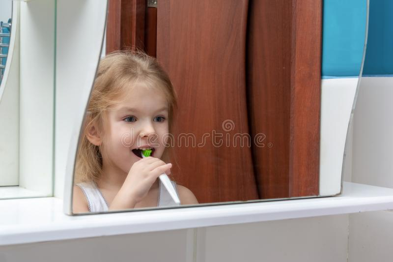The mirror reflects how a little girl with blond hair brushes her teeth. The baby is smiling. royalty free stock photo