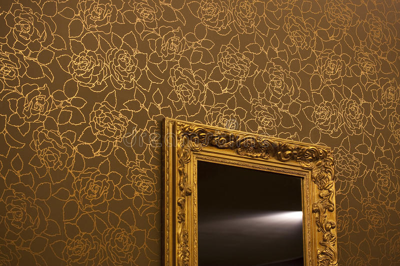 Mirror on the walpaper golden wall. Golden mirror on wall paper golden brown walls in SPA center stock images