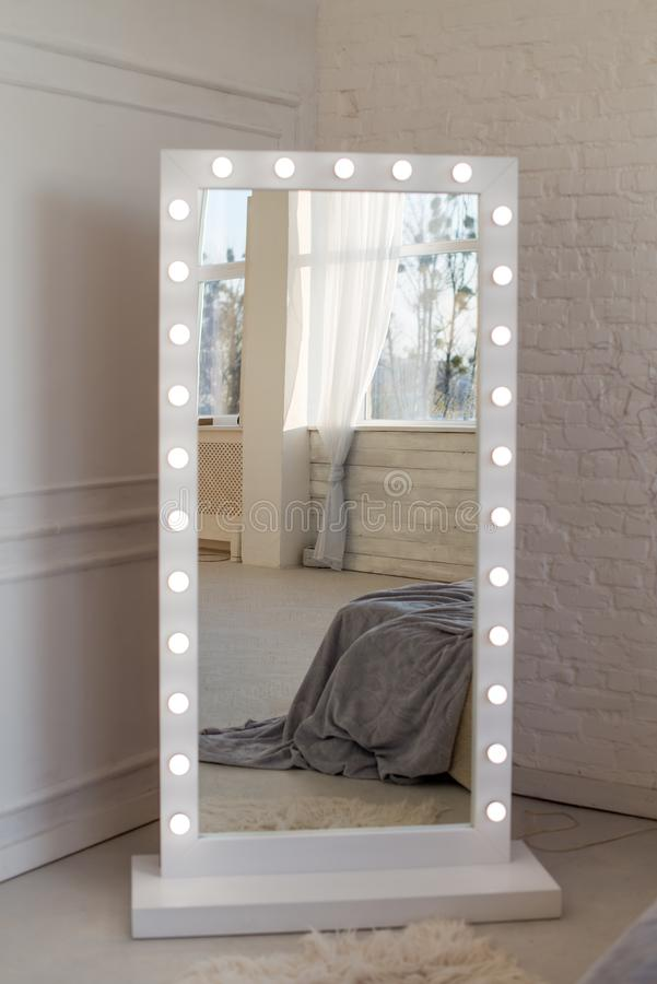 Mirror whith white frame and light bulbs in interior flat. Close up royalty free stock photos
