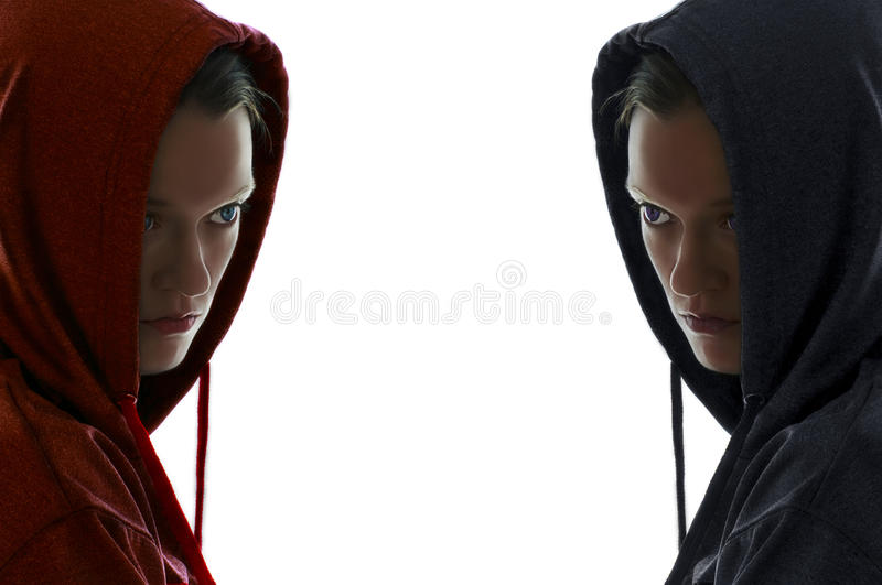 Mirror woman faces. Mirrored image of a caucasian womans face one wearing a red hooded sweatshirts with green blue eyes and the other female wearing a dark blue royalty free stock images