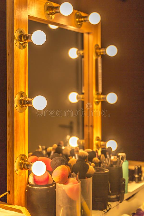 Mirror with wooden frame and spotlights used for professional makeup. Beautiful image of a mirror with wooden frame and spotlights used for professional makeup royalty free stock photo