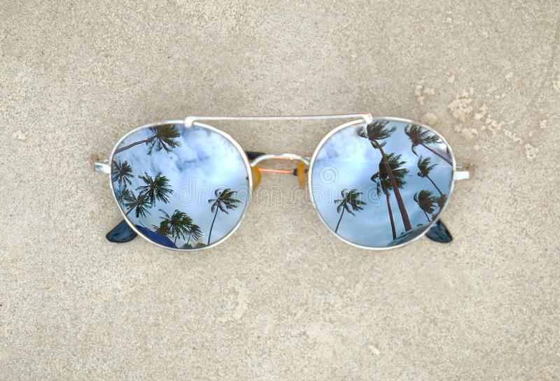 Mirrored sunglasses close up on the beach sand with palm trees reflection stock photos