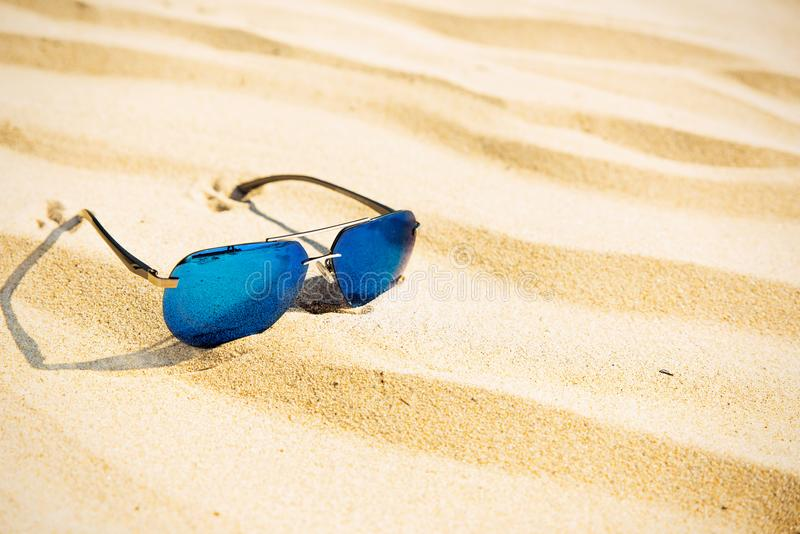 Mirrored sunglasses on a sandy beach. Selective focus. Beach accessories on the sand. holiday season Copy space stock images