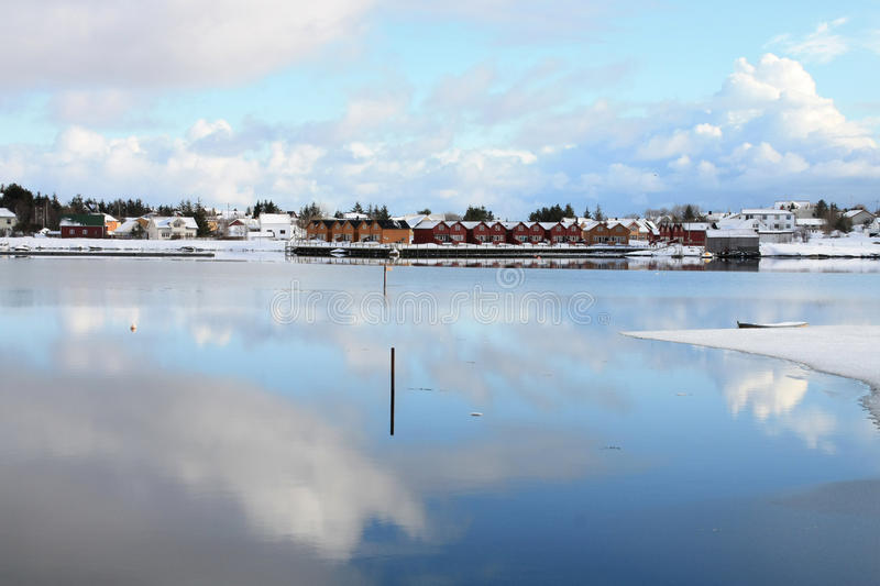 Mirroring Ballstad. The village of Ballstad in Lofoten and the clouds mirroring in his fjord royalty free stock image