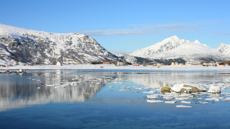 Mirroring in the fjord of Napp. The small village of Skreda mirroring in the Napp's fjord stock photo