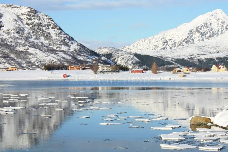 Mirroring in Lofoten's fjord. The small village of Skreda mirroring in the fjord stock image