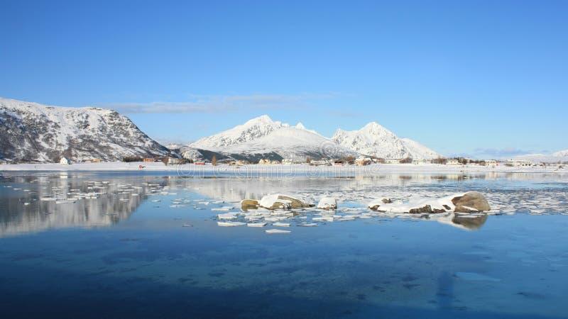 Mirroring in the Lofoten's fjord of Napp. The small village of Skreda mirroring in the Napp's fjord stock photos