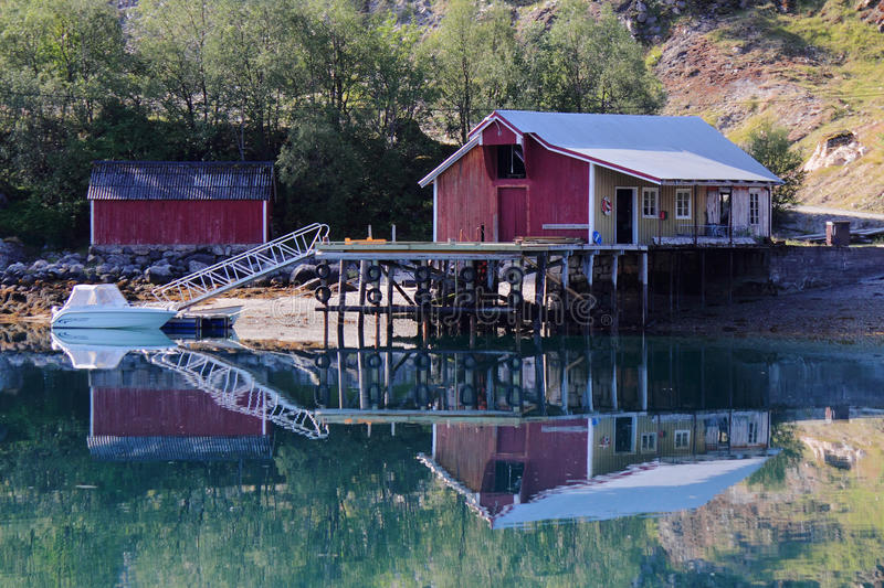 Mirroring old pier of of Holandsfjord. Typical fishermen's and farmers small settlement , Norwegian polar circle royalty free stock photography