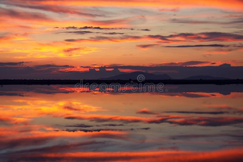Mirroring waters at sunset. Cloudy sunset reflected in the tranquil waters of Messolongion lagoon at spring time stock photos
