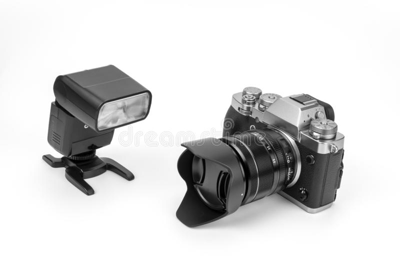 Mirrorless black Camera. View of a Mirrorless black camera isolated on a white background with a flash gun royalty free stock photos