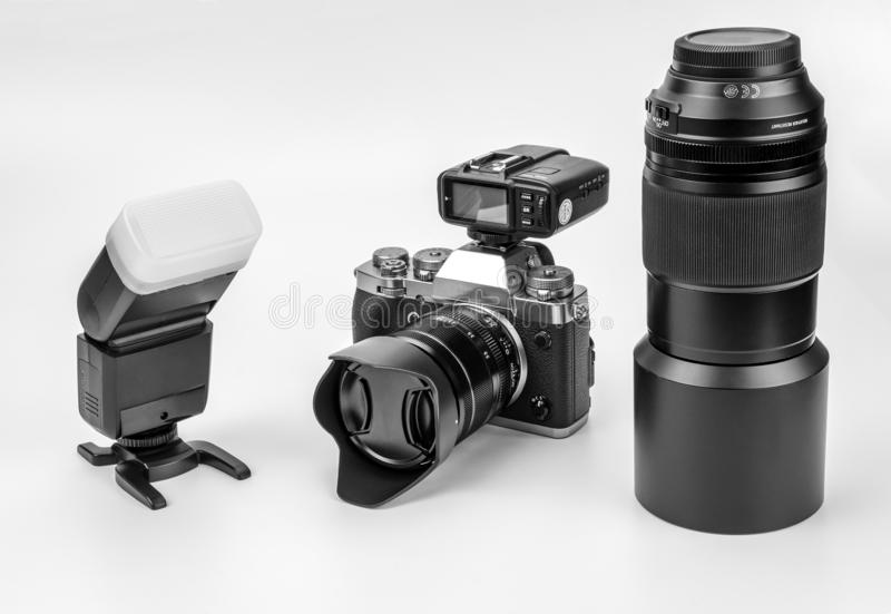 Mirrorless black Camera. View of a Mirrorless black camera isolated on a white background with a flash gun and lenses royalty free stock photos