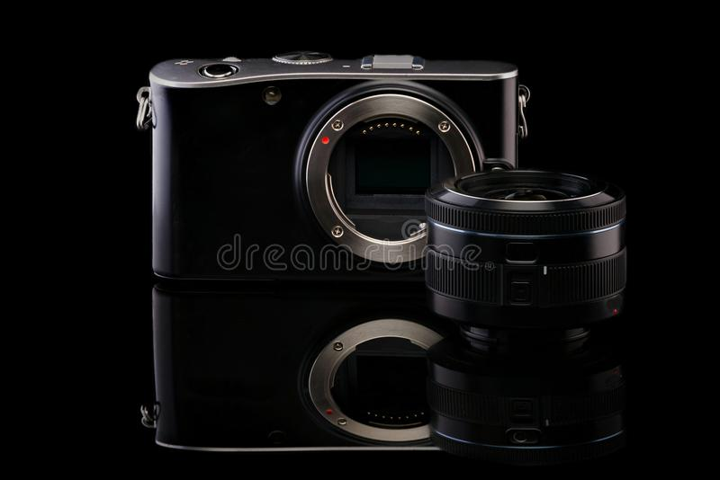 Mirrorless camera body and lens.Isolated on black background. stock photo