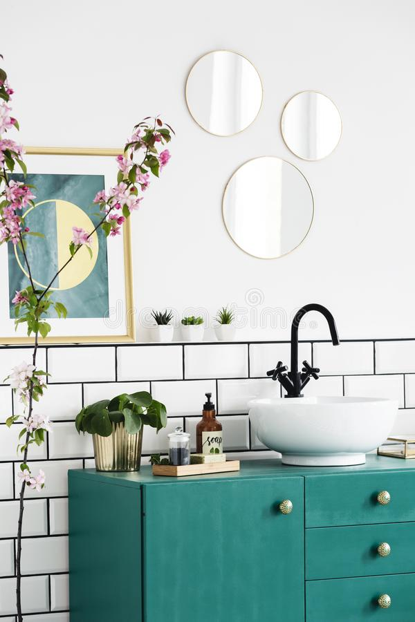 Mirrors and poster above green cabinet in modern bathroom interior with plants. Real photo stock photography