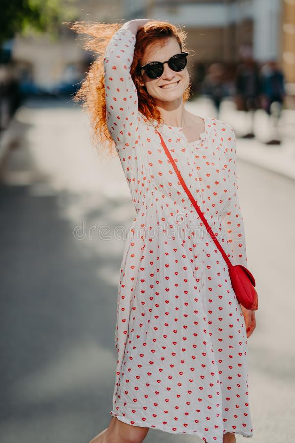 Mirthful young lady strolls on street, has long red hair, wears stylish dress, sunglasses, enjoys sunny day at weekend, poses over royalty free stock image