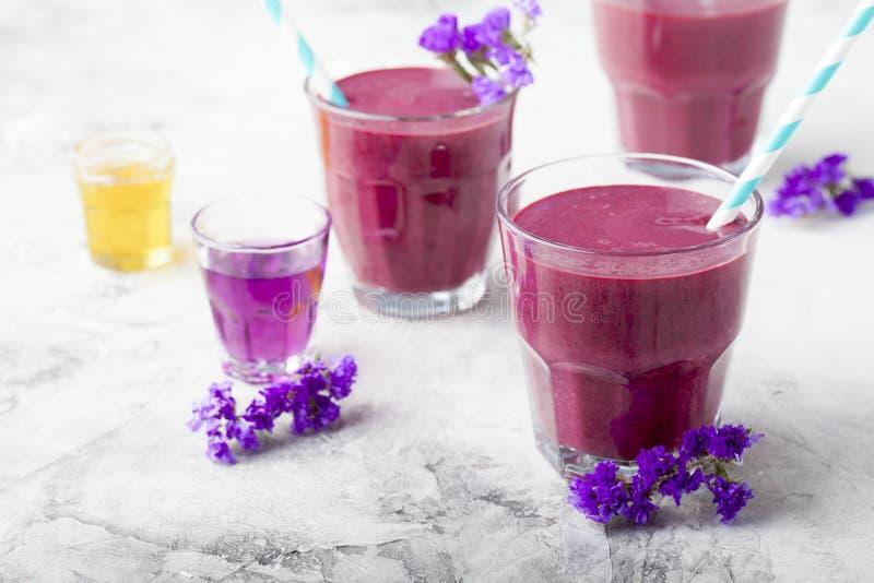 Mirtillo, mora, caprifoglio, frullato honeyberry con sciroppo viola e acai immagini stock
