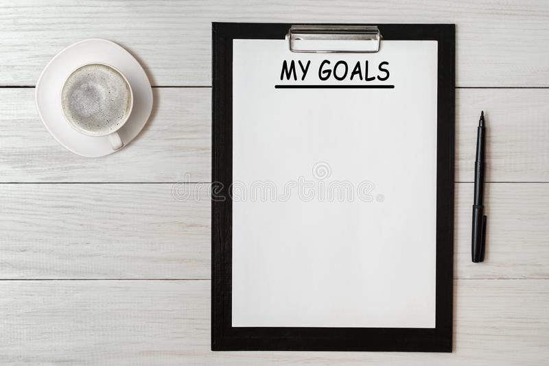 Mis metas enumeran en el papel del cuaderno de notas con la pluma y el café en la tabla de madera imagen de archivo libre de regalías