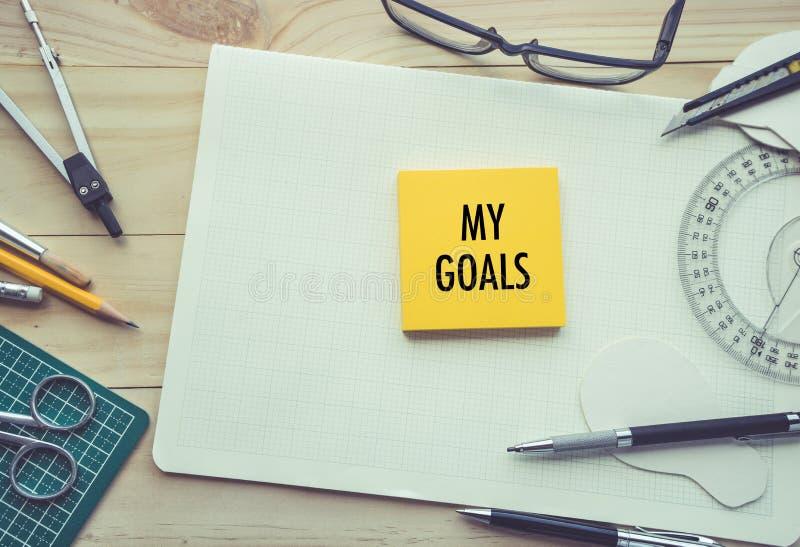 Mis metas mandan un SMS con la libreta en la tabla de trabajo con los elementos de herramientas, fotografía de archivo