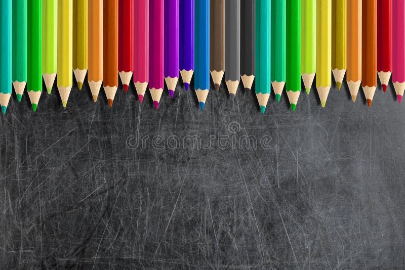 Misaligned coloreó la pizarra en blanco de la pizarra de los lápices foto de archivo