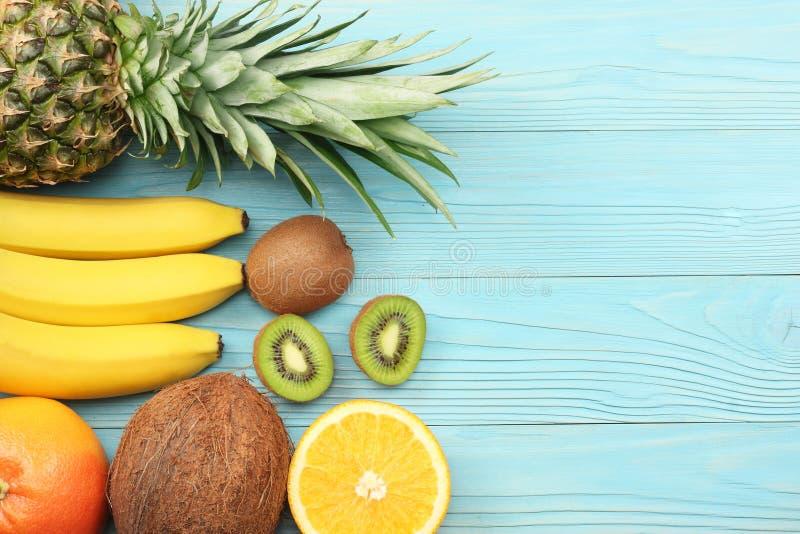 miscela della noce di cocco, della banana, del kiwi, dell'arancia e dell'ananas freschi su fondo di legno blu Vista superiore con fotografia stock libera da diritti