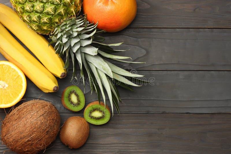 miscela della noce di cocco, della banana, del kiwi, dell'arancia e dell'ananas freschi su fondo di legno scuro Vista superiore c immagine stock