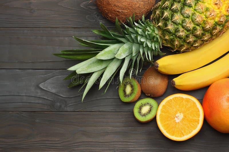 miscela della noce di cocco, della banana, del kiwi, dell'arancia e dell'ananas freschi su fondo di legno scuro Vista superiore c fotografia stock libera da diritti