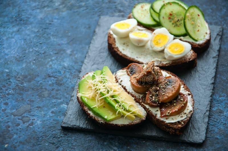Miscela delle Bruschette del pane di segale con vario materiale da otturazione Avocado Mashr fotografie stock