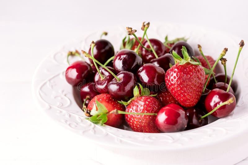Miscela delle fragole e della ciliegia nella bella fragola succosa matura ed in Cherry Close Up del piatto bianco immagine stock