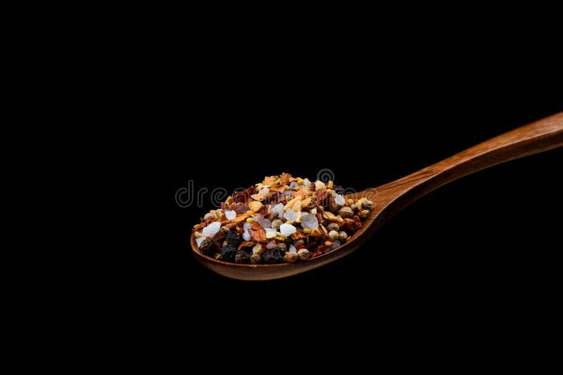 Miscela delle spezie per il mulino culinario sul cucchiaio di legno sopra fondo nero fotografia stock libera da diritti
