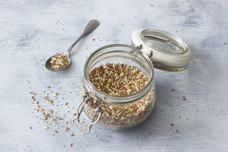 Miscela per i cracker sani del cheto dei semi di chia, lino, sesamo, semi del cereale di zucca di messa a terra in un barattolo d immagini stock