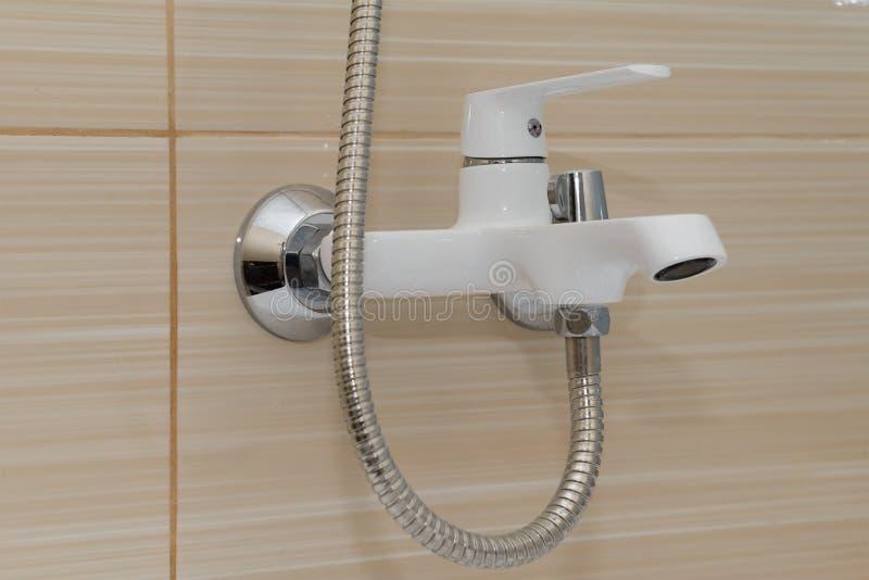 Miscelatore bianco con il tubo flessibile sulla parete fotografie stock libere da diritti