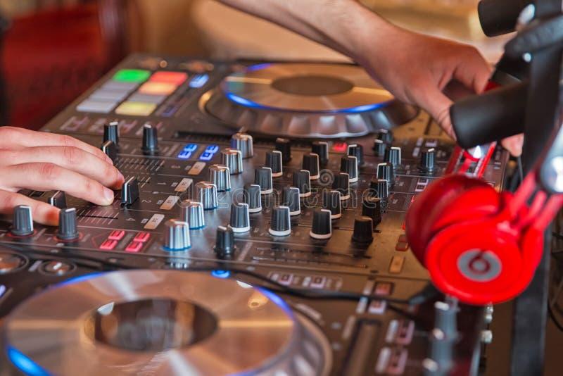 Miscelatore del DJ con le cuffie al night-club Il DJ mescola la pista nel night-club al partito Il DJ mescola la pista nel night- fotografie stock libere da diritti