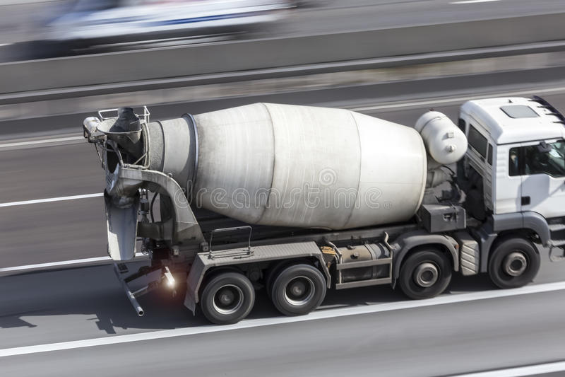Miscelatore di cemento su una strada principale fotografia stock