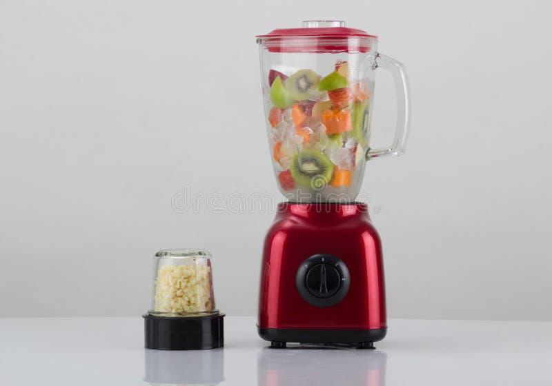 Miscelatore rosso con frutta all'interno e chopper all'aglio isolato su bianco fotografia stock libera da diritti