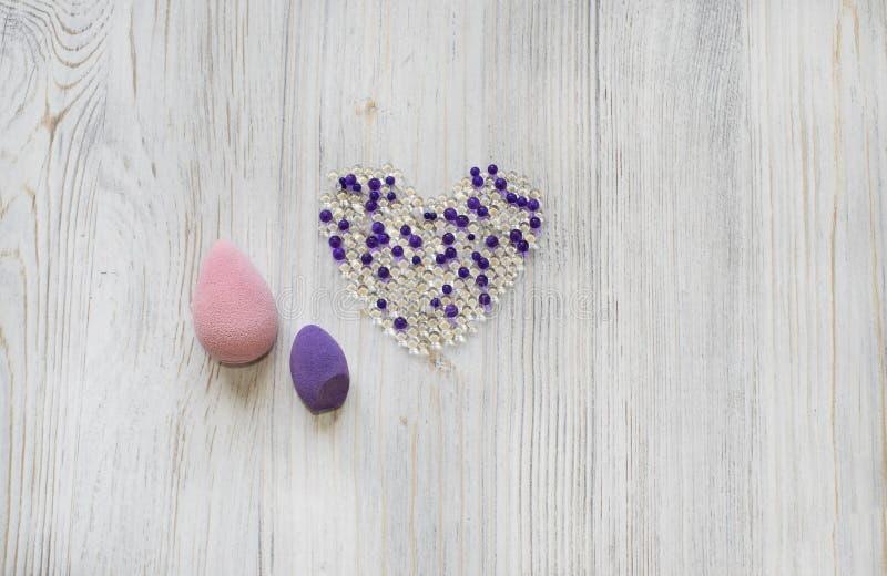 Miscelatori viola e di rosa di bellezza, spugne su fondo grigio di legno Strumenti cosmetici per trucco e palle dell'idrogel sott fotografia stock libera da diritti