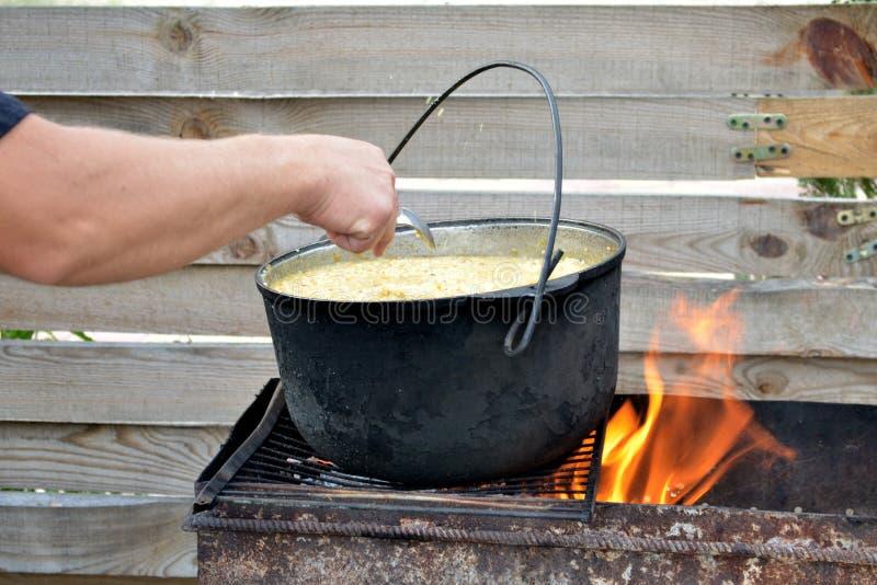 Miscele della mano di un uomo dal porridge del miglio del cucchiaio in un vaso sulla griglia con fuoco, sui precedenti di legno d fotografie stock libere da diritti