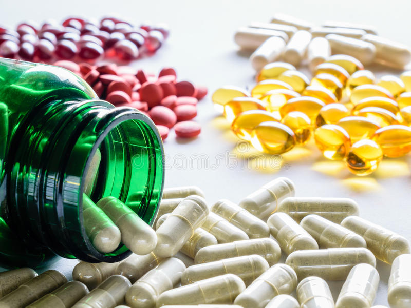 Miscellaneous Groups of Pills. Closeup green bottle spillover with various groups of supplements and pills to include iron, cod liver oil, neem supplements and stock photography
