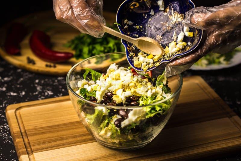 Mischen der Bestandteile des Salats, des Kopfsalates, der Eier und des Gemüsepaprikas der schwarzen Bohne in einer Glasschüssel lizenzfreies stockbild