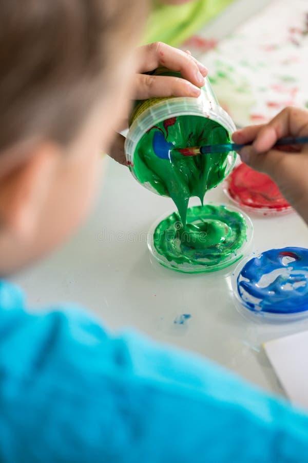 Mischende Farben des kleinen Jungen für seinen Kunstunterricht stockbilder
