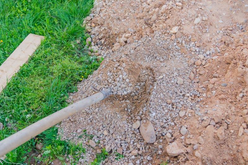 Mischender Beton und Kies der Arbeitskraft mit Spaten auf Bau zitiert lizenzfreie stockfotos