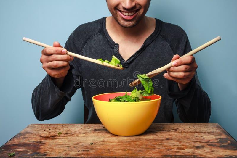 Mischender Salat des glücklichen Mannes mit hölzernen Löffeln lizenzfreies stockfoto