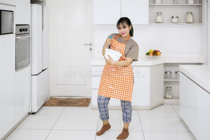 Mischender Teig der hübschen Hausfrau in der Küche stockfoto
