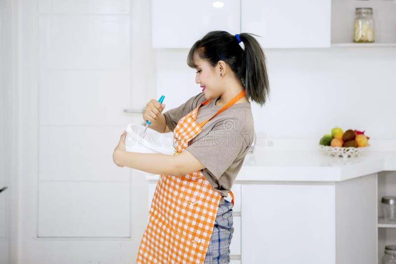 Mischender Teig der jungen Frau im Küchenraum stockbilder