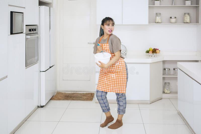 Mischender Teig der jungen Hausfrau in der Küche lizenzfreie stockfotos